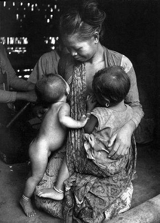 Mujer mongol amamantando a un bebé y a un niño pequeño